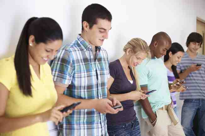 Portrait of a college students reading text message on mobile while standing in a row, copyright PixDeluxe iStock_000014390567