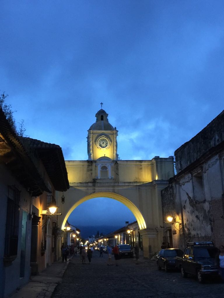 Antigua, Guatemala, at night, with the famous yellow Santa Catalina arch and its clock tower against a cloudy, vivid blue evening sky. Photo by Gwyn Nichols, October 2017.