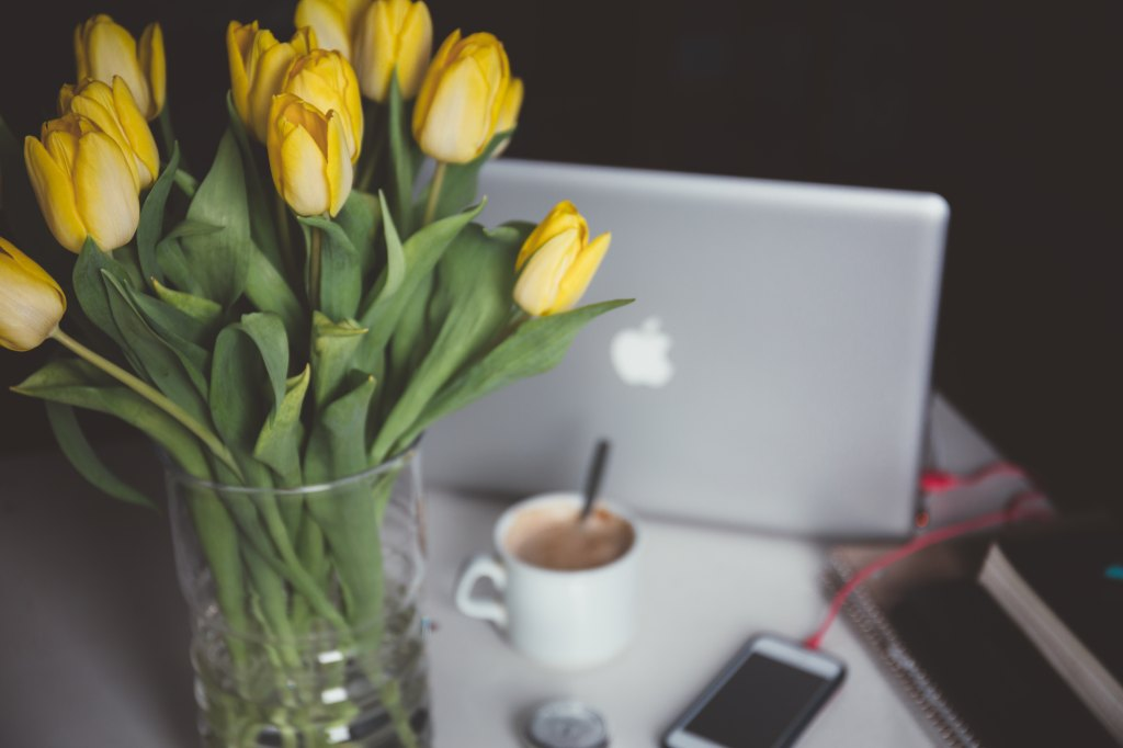 MacBook and iPhone with a vase of yellow tulips and a cup of hot chocolate representing this usability study. Photo by Alisa Anton, Unsplash.